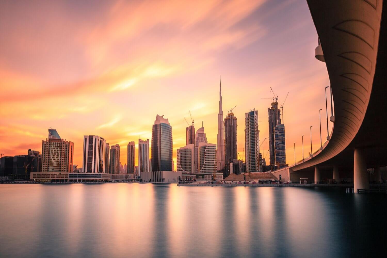 view from the water under a bridge towards Burj Khalifa