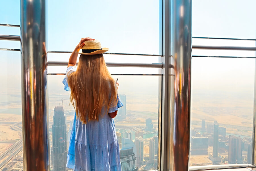 Lady looking out of the window at Burj Khalifa observation deck