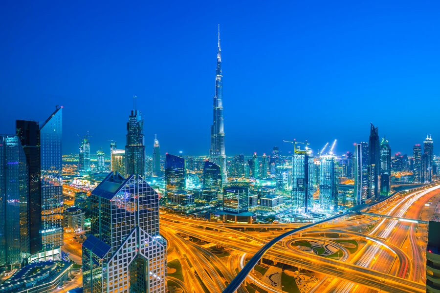a nighttime view of the large intersection in downtown dubai in front of Burj Khalifa