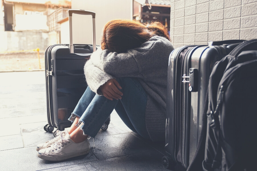 Sad young woman with suitcases