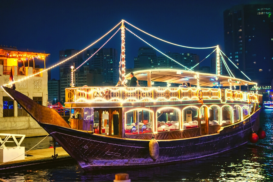 A Dubai traditional dhow boat for dinner cruises lit up at night