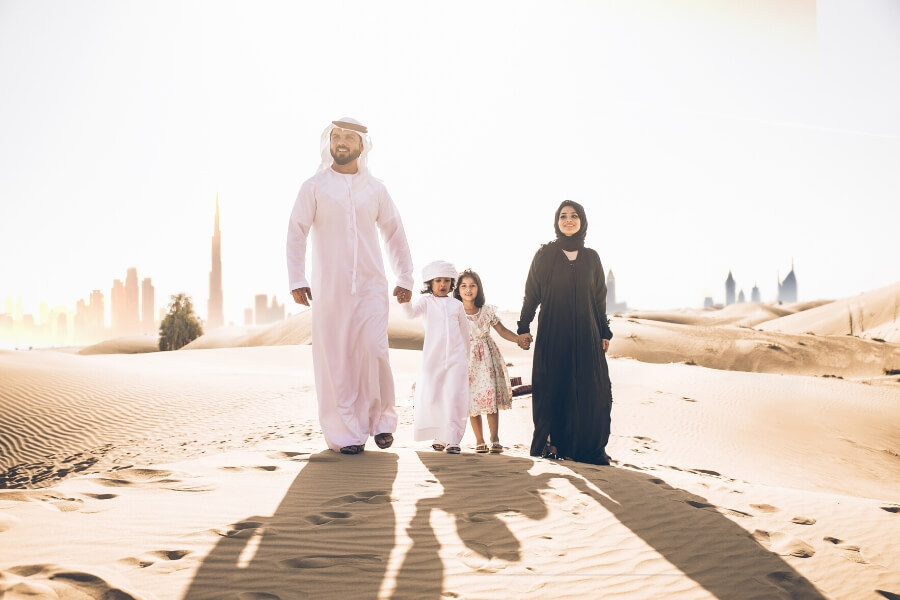 Emirati family walking in the desert outide Dubai