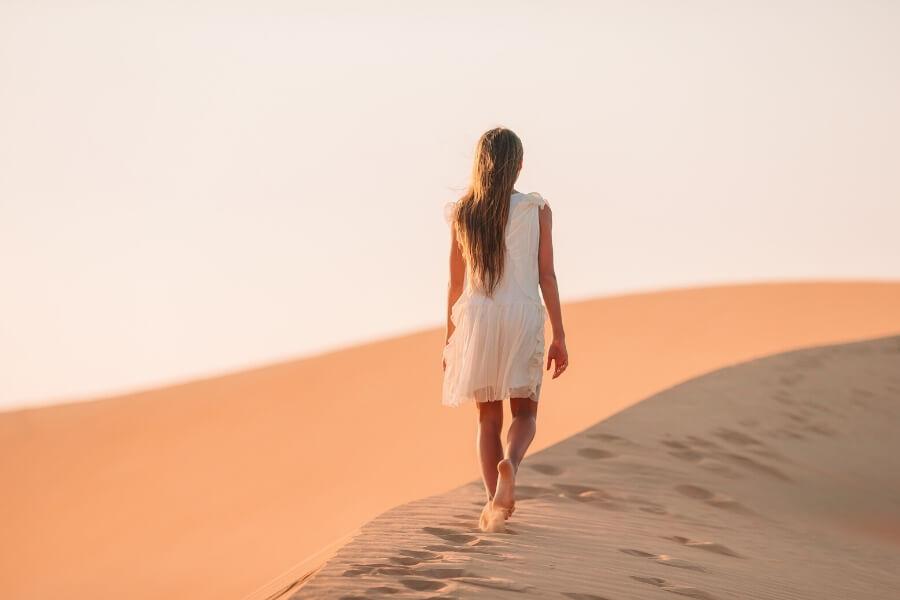 girl walking through the dunes in the Dubai desert
