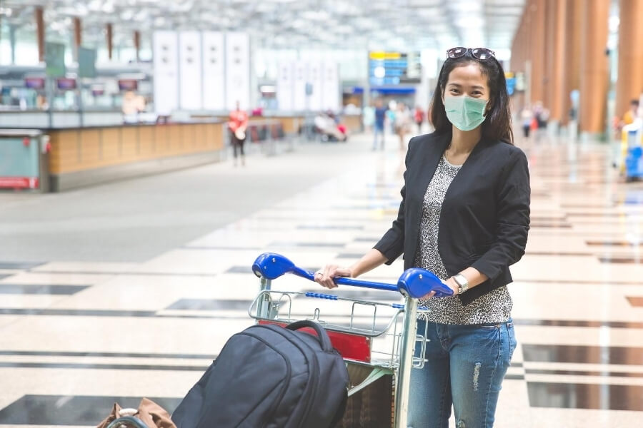 women in mask at an airport - Dubai covid requirements