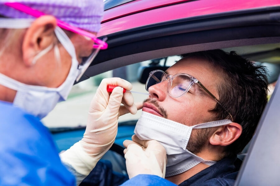 Man having a PCR covid test in a pink car