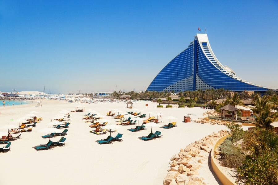 view of the beach front of Jumeirah Beach Hotel with deck chairs