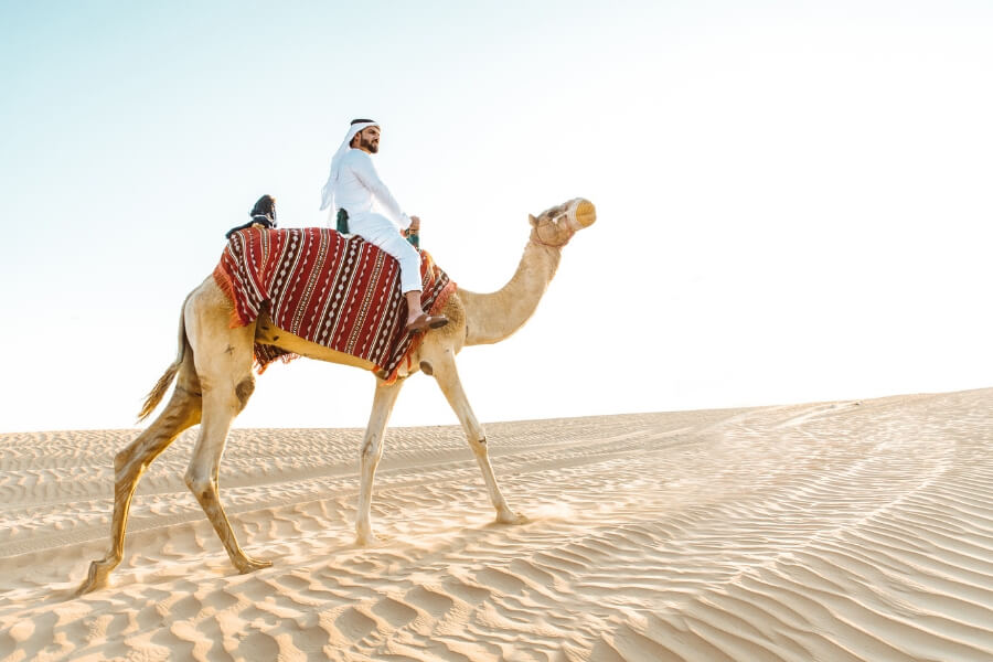Man in modern Emirati dress riding a camel in the UAE Desert - feature image for a 6 day itinerary in Dubai