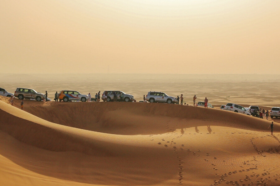 a line of 4wd on a sand dune in the dubai desert at sunset