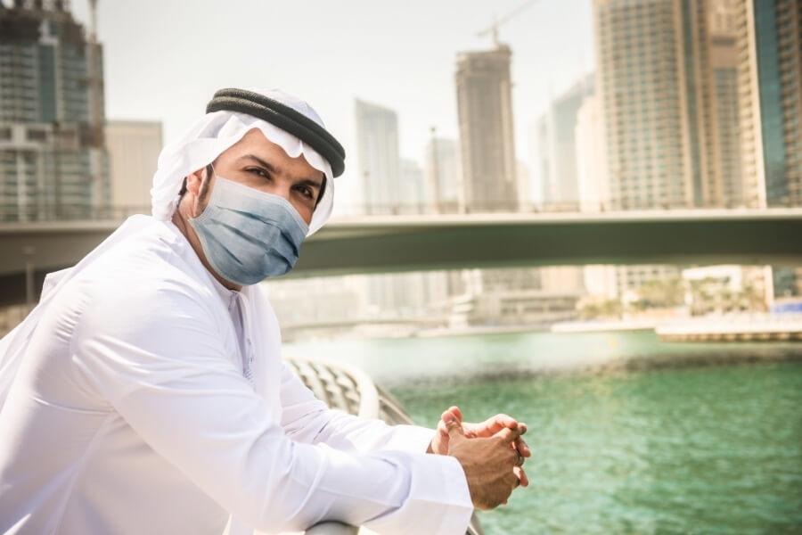 Emirati man in face mask overlooking water in Dubai